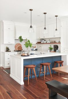 "A bit of blue gray paint on the peninsula did the trick. ""It's just enough color so the kitchen doesn't feel all white,"""