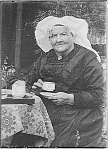 Mevrouw Paans draagt hier een prachtige krullenmuts of keuvel met grote meestal gouden krullen (hoe edeler het metaal en hoe meer windingen, des te rijker). Deze muts is onderdeel van de klederdracht die op de Zuid Hollandse eilanden werd gedragen. Dordrecht 1927 - Regionaal Archief Dordrecht #ZuidHolland #Dordrecht