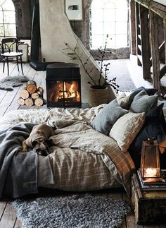 Wood floors with cozy rugs scattered, basket with branches, neutrals and textures. Comfortable, cozy, inviting.