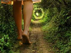 Na imagem: mulher com os pés descalços, andando no meio de uma floresta.