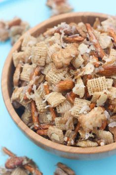A wooden bowl filled with Chex cereal, Teddy grahams , pretzel sticks, almonds, and coconut and topped with a corn syrup mixture to make a chewy snack mix.