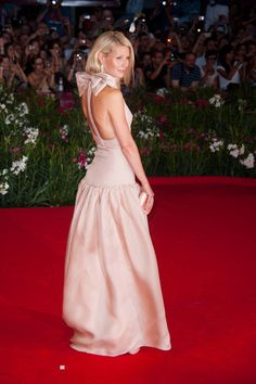 GWYNETH PALTROW stunning in blush-nude gown with great bow at back of neck.