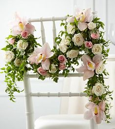 The FTD® Orchid Rose™ Chair Décor takes any reception décor to a new level of sophistication. Pink Cymbidium Orchids and white and pink spray roses are arranged in an elegant manner with variegated ivy vines and smilax garland to be draped on the back of a standard chair, adding that extra special touch to your wedding day. Approximately 48-inches in length.