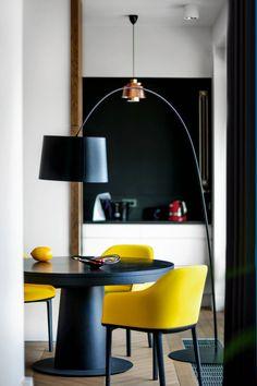 Kuchnia widziana z jadalni przypomina martwą naturę na czarnym tle. Lampa Twiggy (Foscarini), stół rozkładany Granada (BoConcept), krzesła Softshell projektu braci Bouroullec (Vitra).