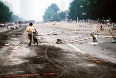 Peter Charlesworth, A lone cyclist walks past street barriers on Changan Avenue hours after the nighttime crackdown on protestors in Tiananmen Square, 1989.