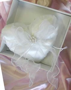 """This beautiful heart-shaped wedding ring pillow in white satin and organza trailing ribbons, with a pearl cluster at the center will keep your wedding ring safe and sound on the day you say """"I do""""."""