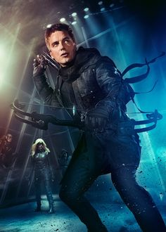 CW Arrow TV Show - Malcolm Merlyn a.k.a. Dark Archer a.k.a. Al Sa-Her readying his weapon of choice in the second, with Flash, Black Canary and Arrow hanging out in the background.
