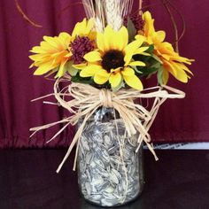 Centerpiece for wedding.  Jar filled with sunflowers seeds to match the theme