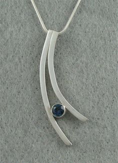 Pendant: sterling silver, tube set London blue topaz. Handmade by Jeanne Boydston. The inspirations for my jewelry come from my own life experiences, observations and imagination. The seed for a new jewelry design may come from an organic form in nature or something as mundane as a light fixture. #handmadesilverjewelry