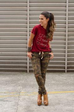 Modelo usa camisetinha vermelha, calça camuflada e open boot tons terrosos.