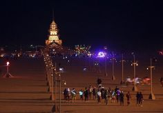 """People walk towards the Temple of Juno, which is alit at night, during the Burning Man 2012 """"Fertility 2.0"""" arts and music festival in the Black Rock Desert of Nevada August 29, 2012. More than 60,000 people from all over the world have gathered at the sold out festival, which is celebrating its 26th year, to spend a week in the remote desert cut off from much of the outside world to experience art, music and the unique community that develops. … (via Burning Man Festival 2012"""