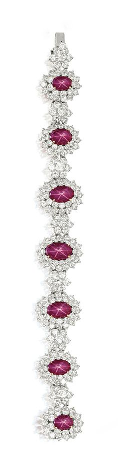 STAR RUBY AND DIAMOND BRACELET    Composed of seven graduated oval cabochon rubies together weighing approximately 30.00 carats, each to a bombé surround of brilliant-cut diamonds, joined by clusters of brilliant-cut diamonds, the diamonds together weighing approximately 22.00 carats, mounted in 18 karat yellow and white gold, length approximately 180mm.