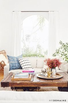 A bright living room with a creme sofa, throw pillows, and a reclaimed wood rolling coffee table