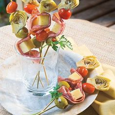 Italian Skewers  1 (8-oz.) block mozzarella cheese  16 (4-inch) Genoa salami slices  1 (14-oz.) can small artichoke hearts, drained and halved  1 pint grape tomatoes  1 (6-oz.) jar large pitted Spanish olives, drained  16 (6-inch) wooden skewers  1 (16-oz.) bottle balsamic-basil vinaigrette  1 tablespoon fresh lemon juice