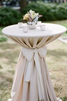 Cocktail Reception Tables, with burlap tie instead?  They would then be used in the main hall by the dance floor and by the bar area too.