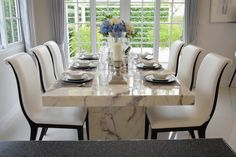 Marble dining table and modern comfortable chairs in a vintage style with six place settings
