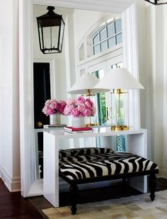 This entry foyer space seems expanded with the use of a propped large framed mirror.  Love the way the entry table anchors the mirror on the floor and repeats the angular shape and white edge.  The zebra print and pink flowers add interest and color.  Notice the small squares of rug and how the shapes are repeated in the transom over the front door.  Repetition ties the space together.  Smart.