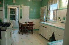 Depression-era kitchen in near-mint condition. Given a complete makeover in the 1930s using the most current materials, the kitchen features floors, countertops and lower walls of original white tile with stunning borders and accents glazed in transparent aqua/seafoam green, while the upper walls and built-in cabinets were resurfaced in matching, aluminum-edged pressboard panels (possibly Marlite, introduced in 1930) for a Streamline look
