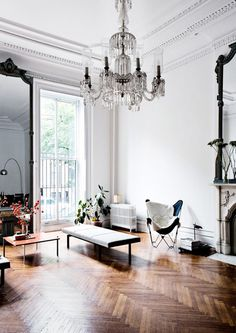 Modern mixed with antiques. Parquet flooring herringbone pattern, large mirrors, chandelier, butterfly chair