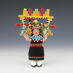 """Zuni beadwork has evolved from tourist souvenirs to detailed pieces of folk art. First the Zuni artists carve a wooden form and then they bead over it, using the peyote stitch and seed or glass beads. With a continuous strand, Zuni beaders meticulously create beautiful patterns throughout their beadwork. This beautiful Maiden was hand beaded by award winning artists Farlan and Alesia Quetawki. Signed 4 1/8"""" tall x 2 3/4"""" long x 1 1/2"""" wide Artist card included"""