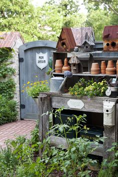 A wooden potting bench, offering a place to begin seedlings, is nestled in a garden bed of herbs and vegetables alongside the outdoor kitchen and dining area.