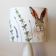 This lampshade, part of my British Wildlife Collection, is oval in shape. This is a beautiful way to display my original designs and you get to see more of the image than on a round lampshade. I have made this lampshade using appliqué, free-motion embroidery and hand-dyed fabrics and wools. It produces a lovely glow when illuminated.