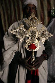 Priest showing the finely carved cross of Asheton Maryam, Lalibela, Ethiopia