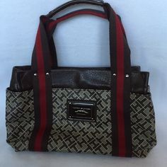 DEAL OF THE DAYTOMMY HILFIGER MONOGRAM HANDBAG TH handbag in like new condition, signature TH pattern with dark brown and red canvas double carry straps. Interior is fabric lined with two slip pockets and one zip pocket. Exterior has small front pocket and two side pockets with snap closure. Tommy Hilfiger Bags