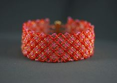 This fun cuff has red seed beads accented with pink and orange woven in to give the appearance of a plaid design. Interspersed is gold for highlights. At this would be a comfortable cuff to wear with any outfit that might need an extra splash of color. Plaid Design, Color Splash, Seed Beads, Weaving, Orange, Bracelets, Pretty, Red, Pink