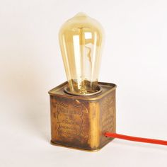 "Perfect for vintage rustic homes or that empty side table screaming for decorative attention. This is a repurposed vintage english breakfast tea brass box from 1940s turned into a cool table lamp with a retro style Edison bulb and red round braided cable. Measures about - height 7.5"" X width 4 (including bulb)"