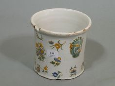 MOUSTIERS  Seau à verre cylindrique à décor polychrome de semis de bouquets de fleurs, les prises en forme de masques de satire.  XVIIIème siècle.  Hauteur: 10,5 cm.