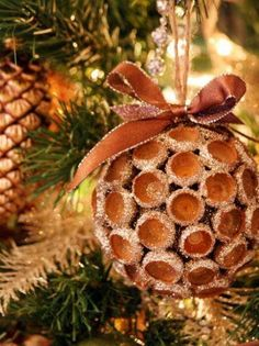 "Natural Christmas Ornament  Look to your own backyard to add nature-inspired elements to your tree. Michelle Edwards of Sweet Something Designs harvested acorns during fall and used the caps to create acorn ball ornaments. ""Paint a Styrofoam ball brown and push the caps in with a dab of hot glue,"" she says. Add some glue to the caps, embellish them with any color glitter to match your tree and top them off with ribbon and twine for hanging. Add glittered pinecones and greenery for a truly…"