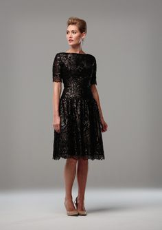 BLACK LACE COCKTAIL DRESS Short sleeved cocktail dress in black lace with sequin flowers, and a delicately scalloped hem and sleeve edge. A dropped waist and lightly gathered skirt.