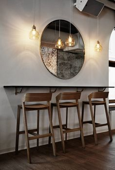 Stylish bar seating area designed by Joanna Laajisto in bar & restaurant Intro, in Kuopio, Finland. The bar stools, lamps and the mirror talk to each other nicely.