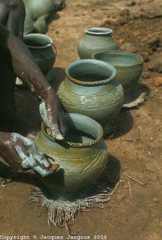Africa, Liberia, Kpelle Tribe: potter decorating clay pots before cooking.