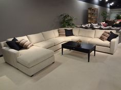 Cream U Shape Canvas Sectional Sofa With Black Wooden Short Legs And Table As