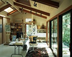 A fairly common way of creating an artist's studio is converting a garage. Here, the existing garage door opening allows easy access to the outside. Other adjustments may include adding skylights (I like the way they exposed the beams here), HVAC and drywall on the inside. This studio makes it clear that storage is an important concern.