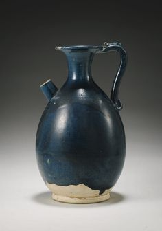 A Very Rare and Finely Potted Blue-Glazed Ewer Tang Dynasty the elegant pear-shaped body rising from a short spreading foot to a trumpet neck and everted flat rim, the shoulder set to one side with a strap handle and to the other with a short cylindrical spout, covered overall in a rich cobalt-blue glaze falling short of the foot to reveal the pale buff body 21.5cm., 8 1/2 in.