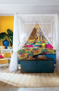 Ralph Lauren Paint's Klimt Gold and an airy canopy bed create a fresh, tropical bedroom