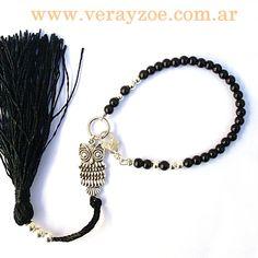 Pulsera con piedras naturales de aghata negra y un dije Buho plateado acompañado por un fleco negro.