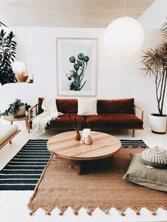 home decor for a living room with a wooden coffee table, rugs, couch, plants, and lots of light