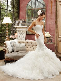 For the bride who loves fabulous frills, modified mermaid Bluebell's simple elegance in misty tulle puts the focus on romance. Swarovski crystals frame the strapless sweetheart neckline while lace appliqués are layered to create a subtly textural bodice with dramatic dropped waist. A corset back closure, chapel length train and removable straps are also included. [...]