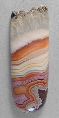 DRYHEAD AGATE  from Montana. Silverhawk's designer gemstones.  This bright and well patterned beauty features fortification banding and a few orbs in shades of reddish-orange, pink and several peach chiffon pastels.