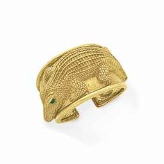 A GOLD AND EMERALD ALLIGATOR CUFF BRACELET, BY DAVID WEBB - Designed as a tapered hinged 18k gold textured cuff, depicting a sculpted alligator with cabochon emerald eyes, mounted in 18k gold, 2 1/8 ins. diameter Signed Webb for David Webb