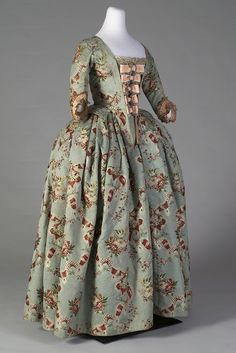 This matching bodice and skirt dates to around 1765. The textile is a magnificent brocaded silk. The close-up photographs give a sense of the texture of the ribbed silk and the brocaded floral patterns. The stomacher with the peach bows is a reproduction, which the Museum Director Jean Druesedow created from silk which she carefully dyed to match and ribbons. 3/4 view - right side 2 Kent State University Costume Museum