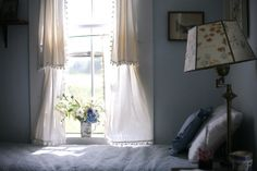 layered curtains and a quaint, little bedroom. Love the poms