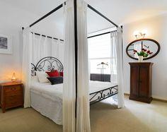 Jedna z ložnic určených pro ubytování hostů je zařízená v lehounkém provensálském stylu. Nebesa nad lůžkem jsou z tenké lněné textilie - ProŽeny.cz