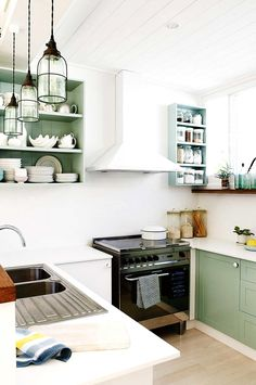 Green and white kitchen with industrial lighting