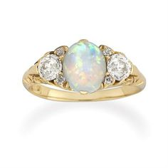 A VICTORIAN OPAL AND DIAMOND RING  A late Victorian opal and diamond three stone carved half hoop ring, the central oval cabochon-cut opal measuring approximately 8.4 x 6.7 mm, an old brilliant-cut diamond set to either side