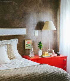 Parede com textura de cimento queimado, criado mudo revestido com contact vermelho e enxoval em cores claras.